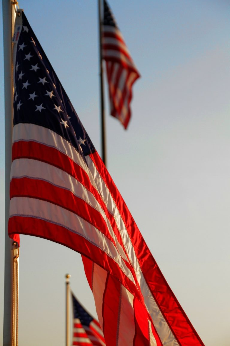 American flag waving, with 2 American Flags in the background.